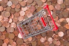 Pièces de monnaie d'euro cent et caddie vide Photographie stock libre de droits