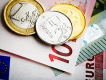 Pièces de monnaie d'euro et de rouble sur d'euro billets de banque Photographie stock libre de droits