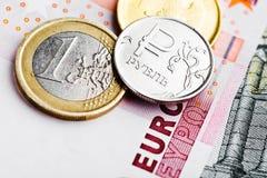 Pièces de monnaie d'euro et de rouble sur d'euro billets de banque Image stock