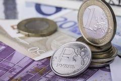 Pièces de monnaie d'euro et de rouble sur les billets de banque européens Photos stock