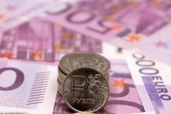 Pièces de monnaie d'euro et de rouble sur d'euro billets de banque photographie stock