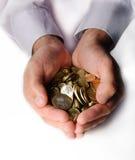 Pièces de monnaie dans des mains évasées Images stock