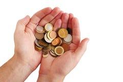 Pièces de monnaie dans des mains de la personne sur un fond blanc Image stock