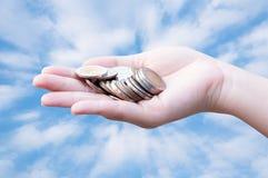 Pièces de monnaie dans des mains sur le ciel bleu photos stock