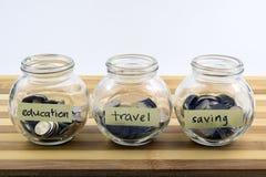 Pièces de monnaie dans des récipients en verre avec des labels sur le bois Photos libres de droits