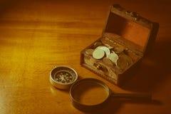 Pièces de monnaie dans le coffre au trésor avec la boussole et la loupe Photo libre de droits
