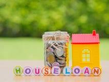 Pièces de monnaie dans le pot avec la maison rouge Image libre de droits