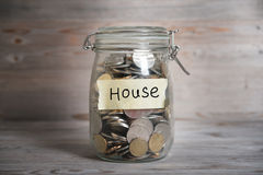 Pièces de monnaie dans le pot avec le label de maison Photos libres de droits