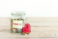 Pièces de monnaie dans le pot avec le texte de charité images stock