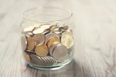 Pièces de monnaie dans le pot en verre d'argent Photos libres de droits