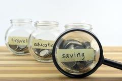 Pièces de monnaie dans le récipient en verre avec le voyage, labels d'économie et d'éducation Images libres de droits