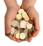 Pièces de monnaie dans les paumes des enfants Images stock