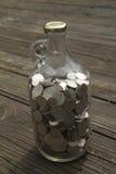 Pièces de monnaie dans une bouteille Photos stock