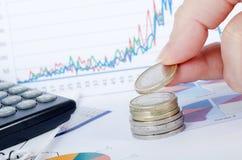 Pièces de monnaie dans une main contre des affaires des tableaux images stock