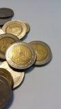 Pièces de monnaie de baht thaïlandais sur le livre blanc Vue supérieure Photographie stock