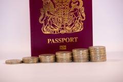 Pièces de monnaie de livre empilées dans l'avant sur le passeport BRITANNIQUE photographie stock