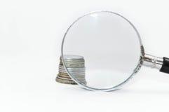 Pièces de monnaie derrière la loupe Images stock