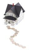 Pièces de monnaie devant le modèle architectural de maison photo stock