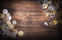Pièces de monnaie de différents pays et de plusieurs vieilles clés sur un vieux panneau en bois, un espace vide pour le texte au  photographie stock