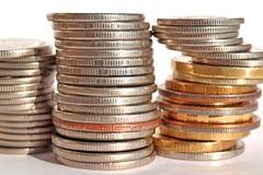 Pièces de monnaie empilées dans les bars Photos stock