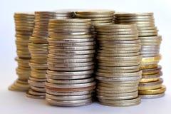 Pièces de monnaie empilées dans les bars Image stock