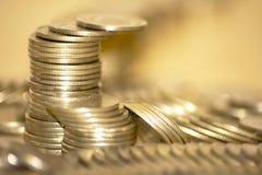 Pièces de monnaie empilées dans les bars Images stock
