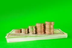Pièces de monnaie empilées dans les bars sur la pile de 100 billets d'un dollar Images stock
