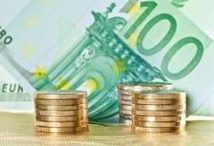 Pièces de monnaie empilées et euro billets de banque Photos libres de droits