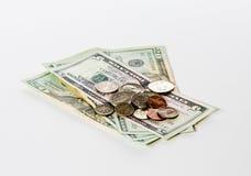 Pièces de monnaie empilées sur des billets d'un dollar Images libres de droits