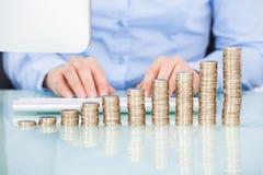 Pièces de monnaie empilées sur le bureau devant la femme d'affaires Photos libres de droits