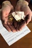 Pièces de monnaie et billets de banque dans des mains sales du ` un s d'hommes photo stock