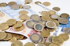 Pièces de monnaie et billets de banque d'euros sur un fond blanc Photo libre de droits