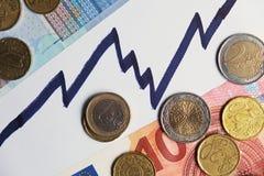 Pièces de monnaie et billets de banque sur une ligne en hausse Photographie stock