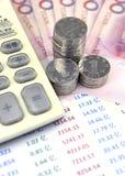 Pièces de monnaie et calculatrice sur le graphique de gestion Images libres de droits