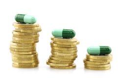 Pièces de monnaie et capsules, dépenses médicales photo stock