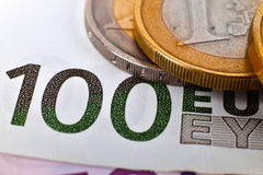 Pièces de monnaie et cent euro billets de banque Images libres de droits