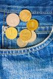 Pièces de monnaie et jeans de poche photos stock