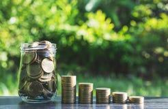 Pièces de monnaie et jeune usine s'élevant sur le sol pour s'enregistrer ou nature c photographie stock