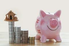 Pièces de monnaie et maison, concept dans la maison de finances, de compte, d'achat et de vente de maison sur la table en bois images stock