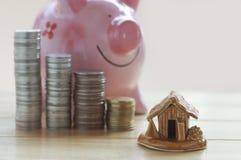 Pièces de monnaie et maison, concept dans la maison de finances, de compte, d'achat et de vente de maison sur la table en bois photos libres de droits