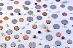 Pièces de monnaie et pilules Photo stock