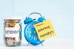Pièces de monnaie et réveil en verre de pot avec du temps à enregistrer l'argent photos stock