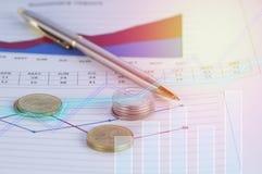 Pièces de monnaie et stylo d'argent sur des écritures des finances et du compte avec le graphique photographie stock libre de droits