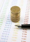 Pièces de monnaie et stylo sur des comptes Photographie stock libre de droits