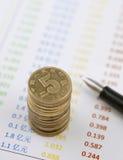 Pièces de monnaie et stylo sur des comptes Photo stock