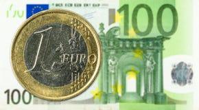 pièces de monnaie de 1 euro contre la face de billet de banque de l'euro 100 photographie stock