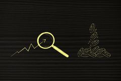 Pièces de monnaie laissant tomber le signe des bénéfices et de la stat positive avec le magnifyin Photographie stock libre de droits