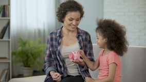 Pièces de monnaie de lancement de maman et de fille dans la tirelire, enregistrant l'argent pour des présents banque de vidéos