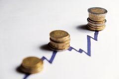 Pièces de monnaie le long des crêtes en hausse d'une ligne de diagramme Image stock