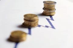 Pièces de monnaie le long des crêtes en hausse d'une ligne de diagramme (EUR, GBP) Photo libre de droits